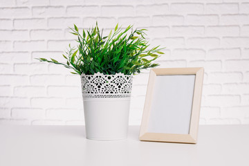 Blank small wooden photo frame and house plant