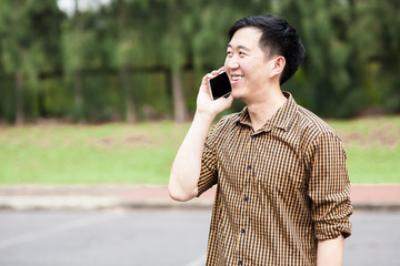 Young Asian man talking on the phone while smiling
