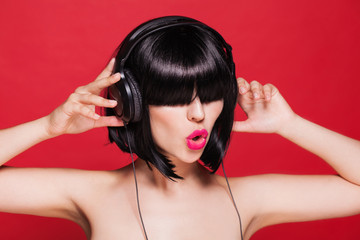 Woman listening to music with headphones enjoying a dance on red