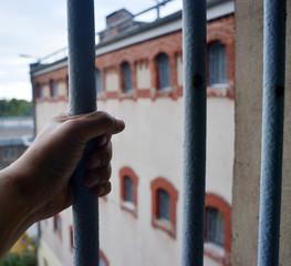 Hand am Gefängnisgitter