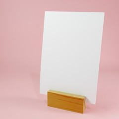 Blank menu card with wooden standing dock on pink background. (#2)