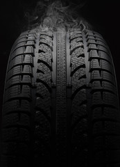 Close-up of car tire with smoke over black background
