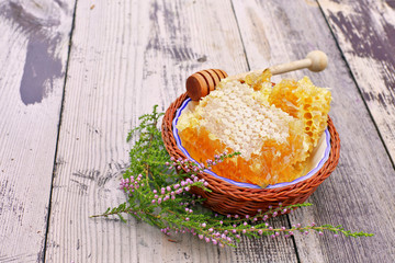 Honey comb in bowl on wooden background
