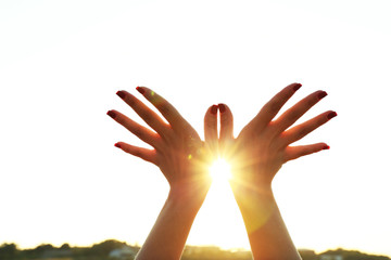 Female hands on sunny sky background