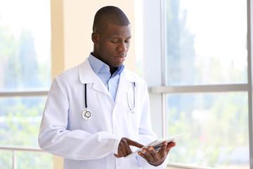 Handsome African American doctor holding digital tablet in hospital
