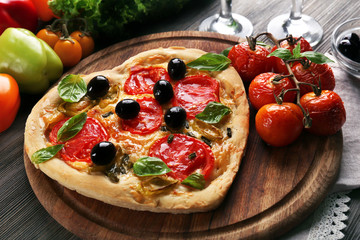 Heart shaped pizza served with wine on wooden table