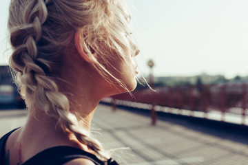 Young woman with braided pigtails. Soft sunny colors.