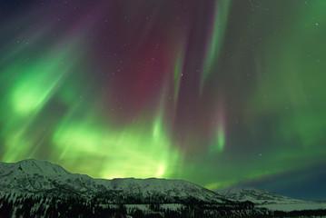 Aurora Borealis over snow capped mountains