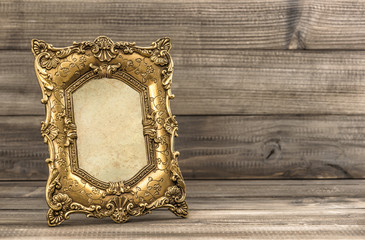 Golden vintage picture frame on wooden background