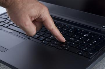 Finger Pressing the Enter Key on a Laptop Keyboard