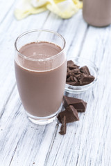 Spoed Foto op Canvas Milkshake Chocolate Milk (on wooden background)