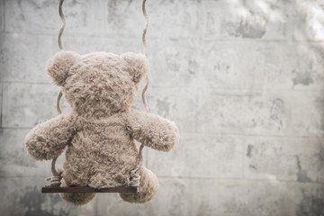 Teddybear on a swing with white wall background