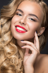 Beautiful blonde girl with curls, red lips and a smile on her