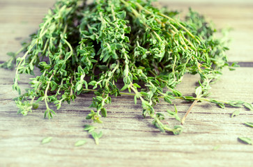 Sprigs of thyme on an old wooden background, selective focus.