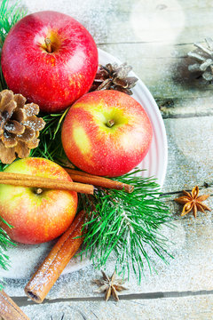 Christmas composition on a platter: apples, tree branches