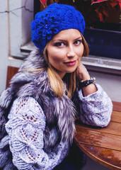 Autumn portrait of a fashionable woman in a blue hat and a fur vest
