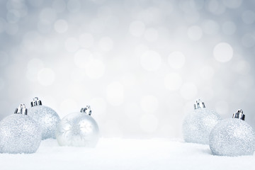 Silver Christmas baubles on snow with a silver background