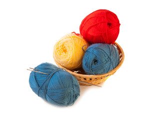 Skeins of yarn in a basket with knitting needles