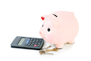 Piggy bank with house keys  and calculator isolated on white