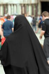 Fototapeta Muslim Traditional Woman - Back view / Traditional Muslim woman with black veil view from behind