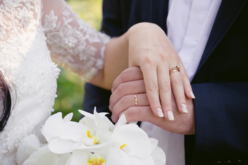 Wedding rings on the hands of newly-weds