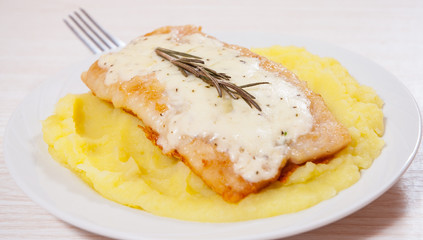 fish fillet under cheese with mashed potatoes