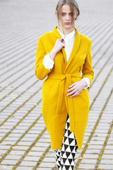 Fashion model in stylish clothes poses outdoors