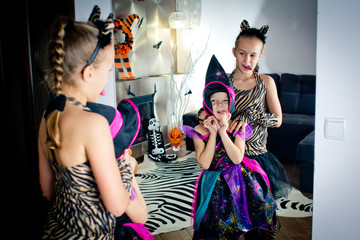 Two girls disguised as a tiger and as a witch are wriggling in front of the mirror in All Saints' Day. Halloween at home.