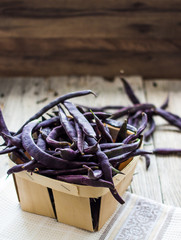 fresh purple string beans on a gray wooden table,.clean eating