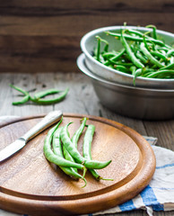 raw green beans on a wooden board and in a colander,knife