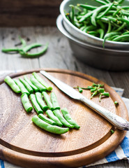 cut with a knife raw.green beans on a wooden board, hands
