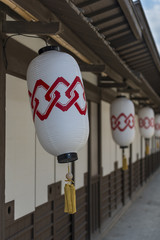 Line of Japanese paper lanterns hanging from a building