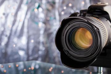 Digitale Spiegelreflexkamera mit Objektiv vor gltzerndem Hintergrund