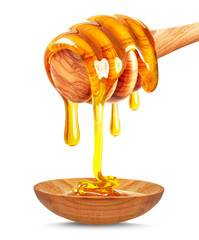 honey dripping on the wooden spoon isolated on white
