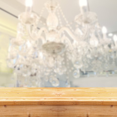 abstract and blurred chrystal chandelier and elegant rustic wood table