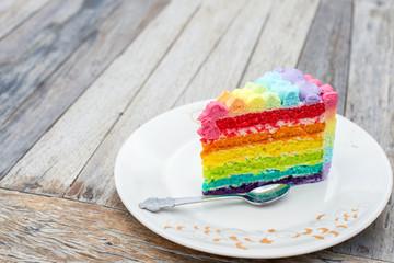 colorful rainbow cream cake on wood table