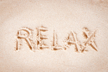 """Text """"Relax"""" writing on sand at the beach, Relax concept."""