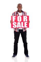 african american man holding a for sale sign
