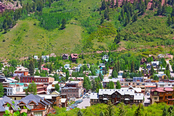 Telluride town surrounded by mountain hillsides, Colorado. Beautiful town at the foot of mountains on a sunny day.