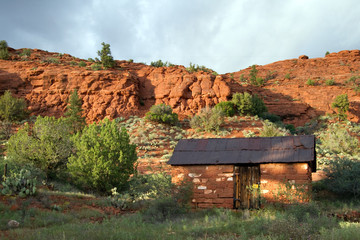 Sunset light on red rocks and an old rock building in Red Rock Crossing park, Sedona, Arizona
