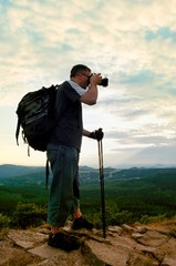 Photographer with big mirror camera on neck and backpack stay on peak of rock. Hilly landscape, fresh green color in valley.