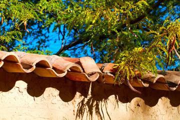 Terra cotta tiles top an adobe wall in Santa Fe, New Mexico