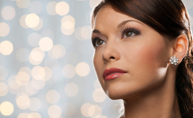woman with diamond earring over holidays lights