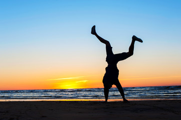 Young man making handstand on the beach. Multicolored sunset bac