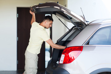 young man with open car trunk at parking space