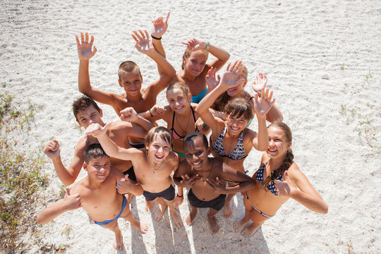 Portrait of happy girls and guys on sand on summer vacation