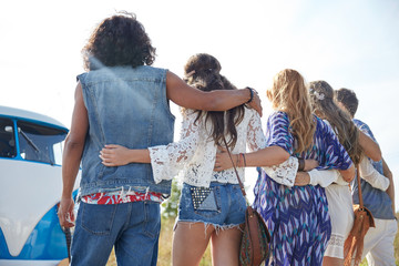 young hippie friends hugging over minivan car