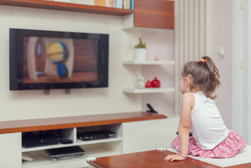 cute little girl having remote control and watching tv at home