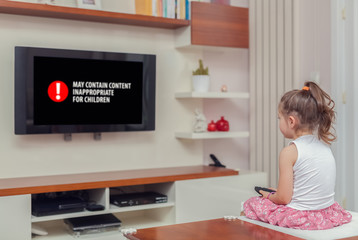cute little girl watching tv. inappropriate content concept.