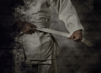 Photo sur Plexiglas Combat Karateka tying the white belt (obi) with grunge background